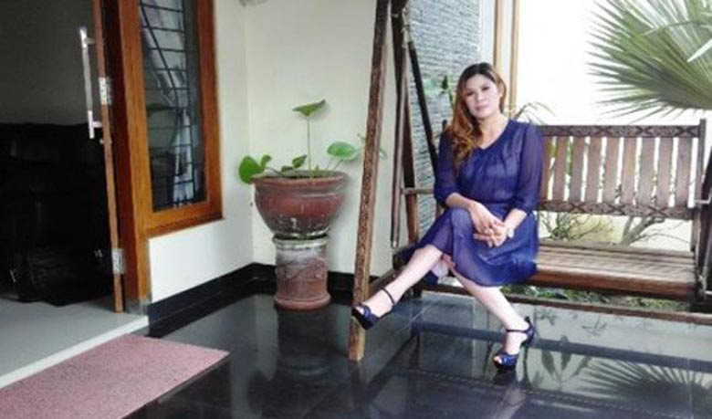 Wina Lia in front of her house